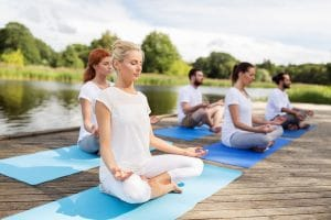 Fitness Sport Yoga And Healthy Lifestyle Concept Group Of People Meditating In Lotus Pose On River Or Lake Berth People Meditating In Yoga Lotus